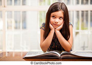 Reading improves imagination - Beautiful little girl reading...