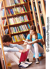 Reading in library - Portrait of teenage friends reading ...