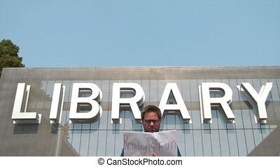 Man in business attire reads book in front of library sign with cover saying reading is fun written in black marker.