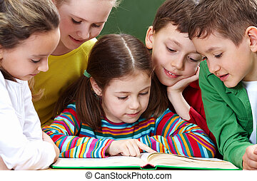 Reading kids - Portrait of friendly group reading book in ...