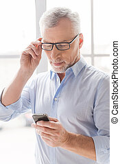 Reading new business messages. Serious grey hair senior man in shirt holding mobile phone and looking at it while standing in front of the window