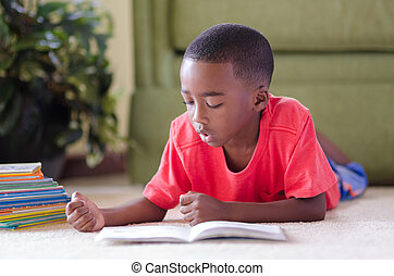 Reading - A young African American boy laying on the floor...