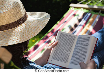 Reading relaxation - A reading woman relaxing on a hammock