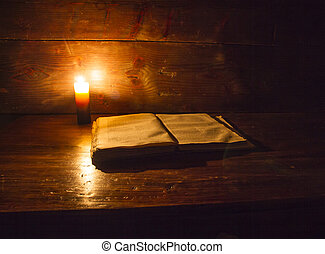 Reading scene in ancient times: an old book leaning on ruined wooden table lighted by a candle on a wooden background