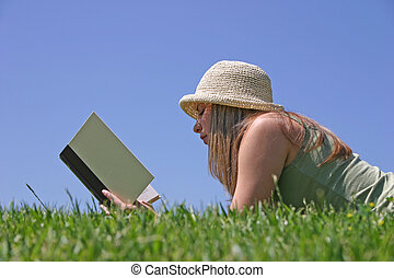 Reading - A young woman reading in the grass.