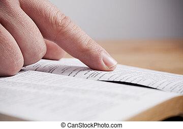 Close up of man reading through the Bible.