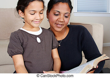 Reading The Bible - Minority woman and her daughter reading...