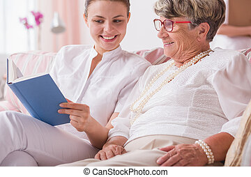 Reading the favourite book story - Smiled nurse and senior...