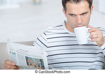 Reading the newspaper as her drinks his coffee