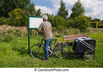Elderly Biker with dog car is reading the route map