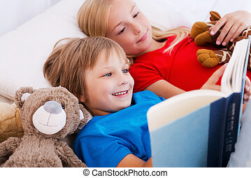 Reading their favorite book. Two cute children reading book...