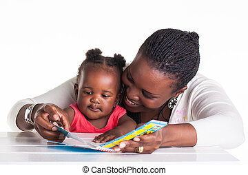 Reading time - Mother is showing some pictures in a book to ...