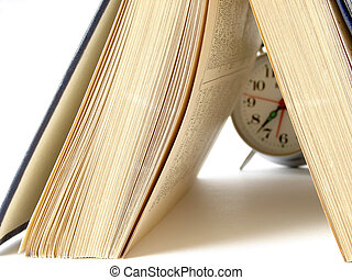 open book and classic alarm clock