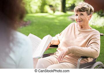 Reading to senior woman