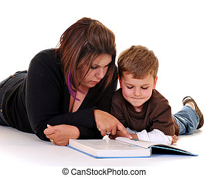 A mother on the floor reading a book to her preschool son. Isolated on white.