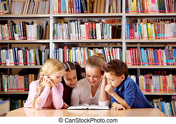 Reading together - Portrait of pupils and teacher looking at...