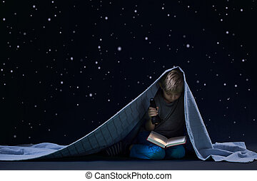 Little boy reading book at night under the blanket
