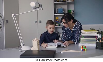 Reading with teacher - an elementary school boy reads aloud to her teacher. Teacher sitting at desk next to male student as they read together.Student and teacher reading a book together in white room at a table