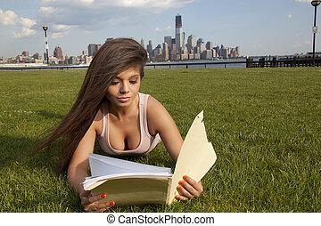 Reading. Woman reading folder in park during summer,