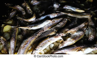 Ready capelin fish dish with potatoes on a dark background in a frying pan top view, slow motion.