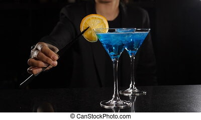 Ready cocktail is on the bar at nightclub. Female bartender decorating cocktail with blue liquid with slice of lemon. Barmaid Decoratingn Alcoholic Cocktail Vermouth Martini with Fresh lemon. Slow motion. Full hd