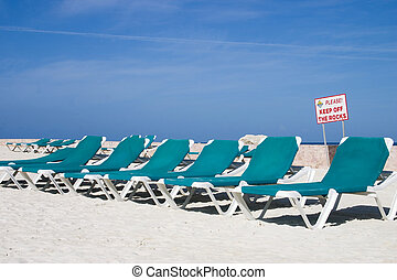 ready for relaxation - beach chairs lined up on at a beach...