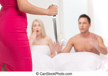 Ready for revenge! Rear view of young women holding a knife while her boyfriend lying on the sofa with another women
