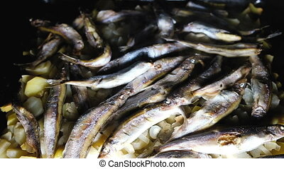 Ready-made dish fish capelin with potatoes on a dark background in a frying pan top view, slow movement.