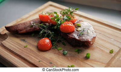 ready-made dish of the restaurant from the chef. a piece of baked meat with tomatoes on a wooden board
