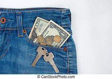 Ready money and keys to the house on a keychain are lying in a side pocket of blue jeans.