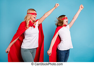 Ready set go. Photo of funny mom lady little daughter spend time together carnival super hero costumes going to fly up raise fists wear s-shirts red coat masks isolated blue color background