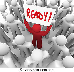 The word Ready on a sign held by a unique red person in a crowd to illustrate being prepared for a test or embark on a journey or challenge