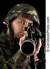 Ready soldier aiming a rifle in studio