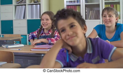 Ready to Answer - Cheerful pupils sitting at desks during...