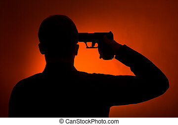 silhouette of the man pointing gun to his head, ready to commit suicide