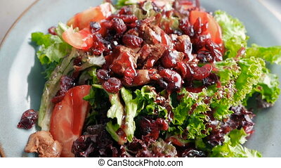 ready-to-eat salad from the chef from dried fruits, tomatoes, lettuce leaves, liver, in a restaurant kitchen. cooking salad step by step