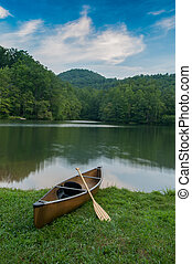 Ready to Float - Single boat with paddle on the shore of a...