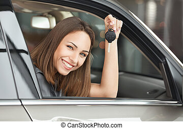 Ready to get on the road. Attractive young woman sitting at the front seat of the car holding a key and looking at camera