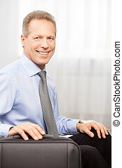 Ready to go. Smiling grey hair man in shirt and tie holding hand on suitcase while sitting on bed