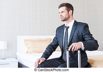 Ready to new business trip. Confident young businessman in formalwear carrying suitcase and smiling while sitting on the bed in hotel room