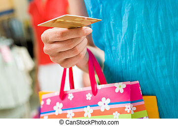 Ready to pay - Image of female holding card in hand ready to...