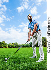 Ready to strike. Low angle view of young man playing golf while standing on green
