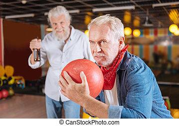 Nice aged man holding a bowling ball