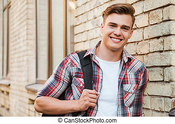 Ready to study. Handsome young man carrying backpack on one shoulder and smiling while leaning at the brick wall