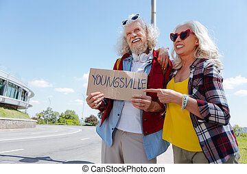 Delighted aged woman pointing at the sign