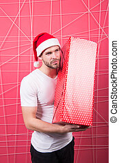 Ready to unpack your gift. Christmas holiday celebration. Man handsome unshaven santa hat hold gift box. Christmas gift concept. Santa bring gift for you. Man attractive santa claus carry big box