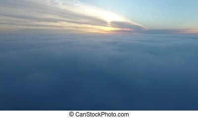 Real Aerial shot, Drone fly in clouds in sunrise nature, camera fly in foggy. Flight over clouds sunrise, ridges and hills in the sunlight of dawn.