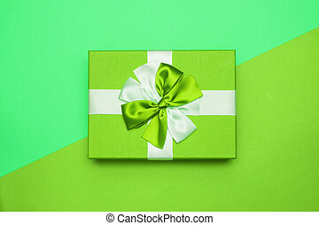 Real box with white and green bow and ribbon top view on Valentine's day isolated on green background. Flat lay. Copy space