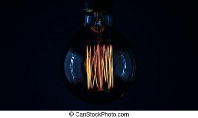 Real Edison light bulb flickering. Vintage filament Edison light bulb. Close up. 4K UHD video.