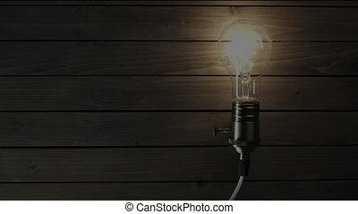 Real Edison light bulb flickering. Vintage filament Edison light bulb. Close up. 4K UHD video. Symbol of idea. The light comes on on a black background.